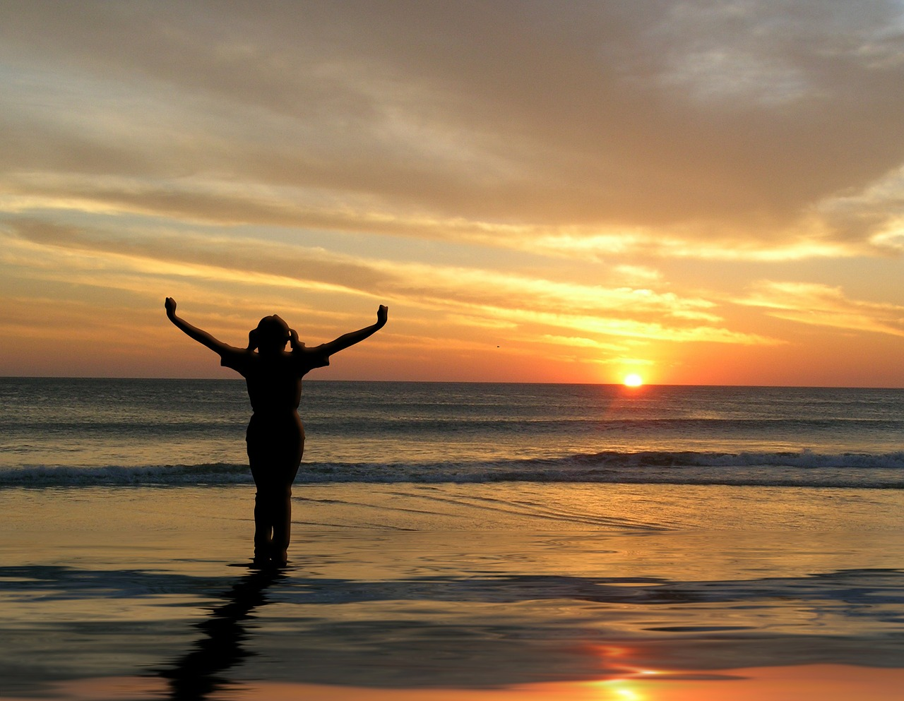 image of girl with outstretched arms looking at sunset